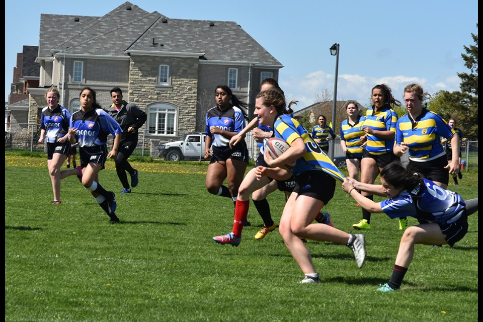 Bradford player (in blue) gets a hand on Eastview runner (in stripes). Miriam King/Bradford Today