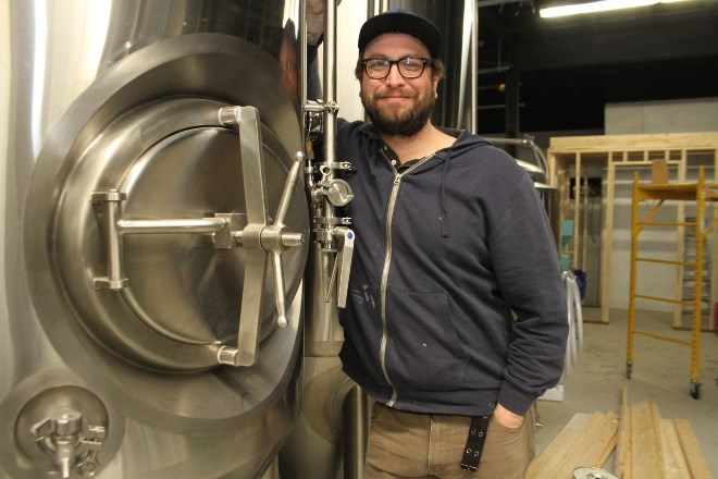 Graham Orser, president and brewmaster of Forty Six North brewing Company, the latest brewery to open in Sudbury, stands with one of the tanks in the soon-to-be brewing and bottling room. (Karen McKinley photo)