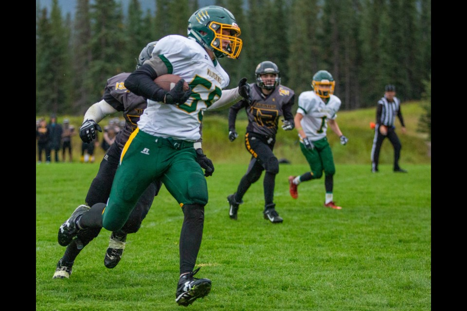 Canmore's Joshua Ellis holds off a Drumheller player as he returns a punt for the Wolverines first touchdown during a game at Millennium Field on Monday (Sept. 9). Evan Buhler RMO Photo