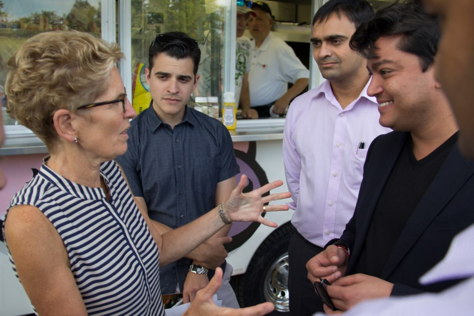 Ontario Premier Kathleen Wynne chinwags last night in Bellevue Park with Ward 3 Councillor Matthew Shoemaker and Essar Global's Amar Kapadia and Rewant Ruia. Photo by Jeff Klassen/ SooToday.